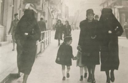 Photo of women and children in street together: A Muslim veiled woman, Zejneba Hardaga (right) and Jewish woman, Rivka Kalb (2nd from right) and her children are guided on the streets of Sarajevo in 1941. Zejneba covered the yellow star on the Rivka's left arm with her veil. Bahrija Hardasa, sister-in-law of Zejneba, is on the far left.